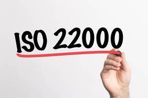 Human hand writing ISO 22000 on whiteboard