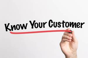 Human hand writing Know Your Customer on whiteboard