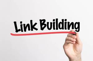 Human hand writing Link Building on whiteboard