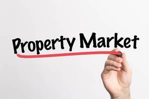 Human hand writing Property Market on whiteboard
