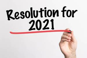 Human hand writing Resolution for 2021 on whiteboard