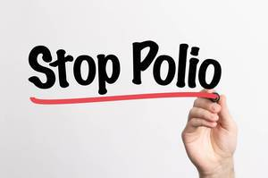 Human hand writing Stop Polio on whiteboard