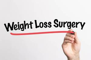 Human hand writing Weight Loss Surgery on whiteboard