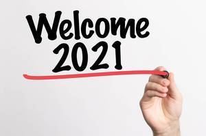 Human hand writing Welcome 2021 on whiteboard