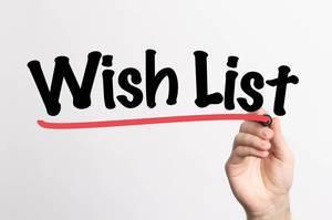 Human hand writing Wish List on whiteboard