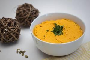Hummus aus Kürbis in einer Schüssel mit Petersilie verziert