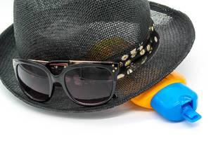 Hut, Sonnenbrille und Sonnenkreme vor weißem Hintergrund