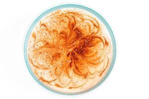 Hüttenkäse-Joghurt mit Kakaopulver in einer Schüssel auf weißem Hintergrund von oben fotografiert