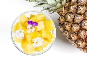 Hüttenkäse mit frischer Ananas, Chiasamen und essbaren Blumen in einer Schüssel, Aufnahme von oben vor weißem Hintergrund