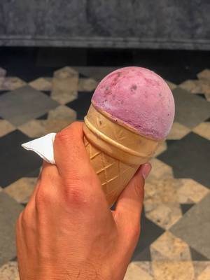 Ice cream cone with a strawberry scoop in hand