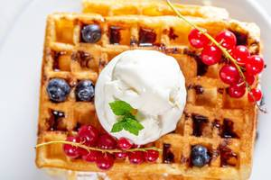 Ice cream with mint leaves and fresh berries on Belgian waffles (Flip 2019)
