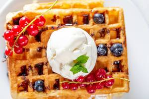 Ice cream with mint leaves and fresh berries on Belgian waffles