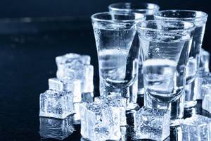 Ice cubes and glasses with cool vodka