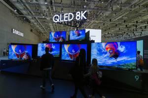 IFA-Messebesucher vor großen Fernsehbildschirmen von Samsung QLED 8K mit AI-Upscaling-Funktion