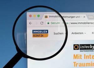 Immobilien Scout 24 Logo am PC-Monitor, durch eine Lupe fotografiert