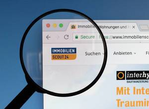 Immobilien Scout 24 logo on a computer screen with a magnifying glass