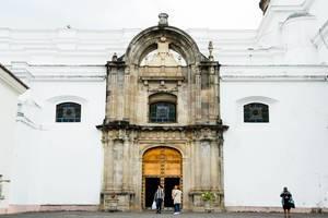 Imposanter, aus Stein gebauter Eingang mit massivem Tor zu einer weißen Kathedrale