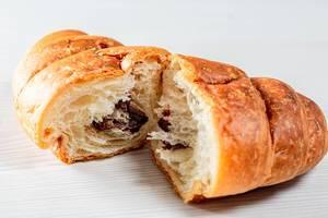 In der Mitte gebrochener, mit Schokolade gefülltes Croissant auf weißem Tisch