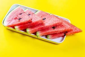 In Dreiecke geschnittene Wassermelone mit Kernen, auf gelber Oberfläche
