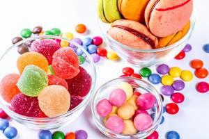 In Glasschüsseln Gummibärchen und Marmelade farbige Süßigkeiten