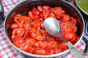 In Scheiben geschnittene, kleine Tomaten in einem Kochtopf