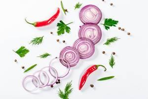 In Scheiben geschnittene rote Zwiebel mit Chilis, Kräutern und Pfefferkörnern auf weißem Hintergrund