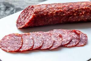 In Scheiben geschnittene Salamiwurst auf einem weißen Schneidebrett