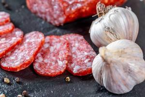 In Scheiben geschnittene Salamiwurst neben Knoblauch und Pfefferkörnern