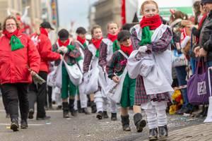 In weiße Kittel gekleidete Kinder werfen Zuschauern Süßigkeiten zu - Kölner Karneval 2018