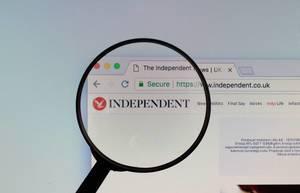Independent-Logo am PC-Monitor, durch eine Lupe fotografiert
