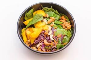 Indian Summer Bowl mit Blattspinat, Zuckerschoten, warme Rosmarin Kartoffeln, Rohkostsalat, geröstete gelbe Karotten, Cashews, Basilikum, Koriander sowie gelbe Thai-Curry Sauce