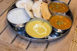 Indisches Mittagessen serviert in Schälchen mit Reis und Fladenbrot