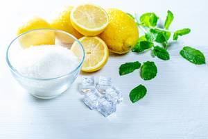 Ingredients for lemonade - sugar, lemons, mint leaves and ice