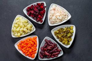 Ingredients for vegetable salad in triangular plates on black background. Top view (Flip 2019)
