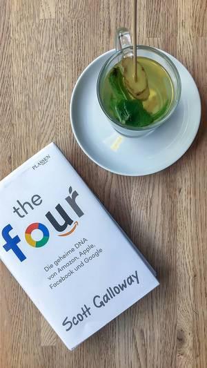 """Ingwer-Minz-Tee im Glas, neben der Leselektüre und dem Social-Media-Entschlüsselungsbuch """"The Four"""" von Scott Galloway, auf einem Holztisch"""