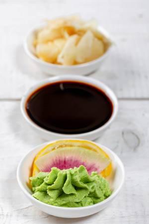 Ingwer, Sojasoße und Wasabi mit Zitrone in weißen Schalen auf einem weißen Holztisch