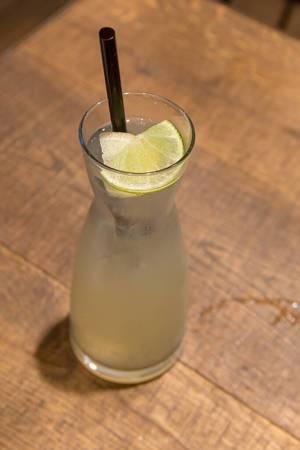 Ingwer-Zitronenlimonade mit einer Scheibe Zitrone und schwarzem Strohhalm in länglichem Glas, auf einem Holztisch