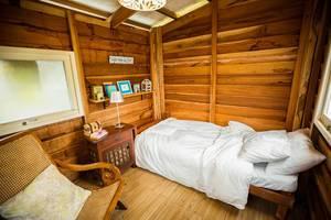 Innenausstattung eines kleinen Holzchalets mit Bett, Stuhl und Nachttisch