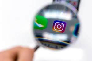 Instagram app on mobile phone photographed through magnifying glass against white background