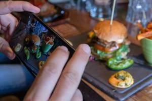 Instagram-Foodblogger fotografiert das Mittagessen: Hamburger mit Pommes-Beilage auf einem schwarzen Tablett auf einem Holztisch im Restaurant