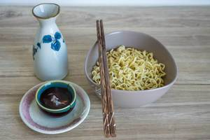Instant Noodle Soup in a Bowl with Chopsticks and small Tea Cup on a Wodden Table