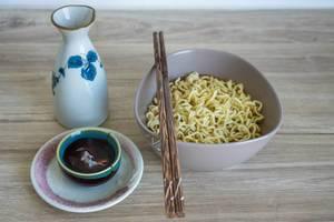 Instant-Nudelsuppe in Schüssel mit Essstäbchen Tee in Schälchen auf Holztisch