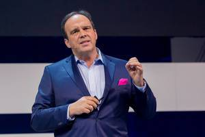 Intense facial expression during a keynote presentation: Hagen Rickmann (Deutsche Telekom) in a blue suit with magenta handkerchief - the colour of his company