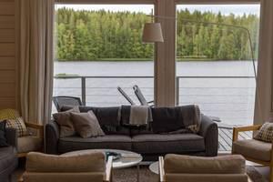 Interieur und gemütliche Sofaecke des Luxus-Ferienhauses Villa Jolla nahe Lahti, mit Wald- und Seeblick auf den Paijänne
