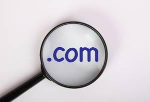 Internationale Domainendung .com in blau auf weiß, vergrößert dargestellt unter einer Lupe