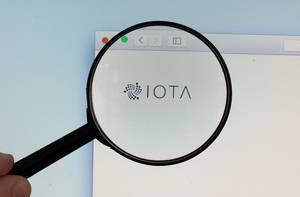 IOTA-Logo am PC-Monitor, durch eine Lupe fotografiert