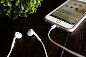 Iphone und Kopfhörer auf einem dunklen Holztisch