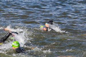 Ironman athletes, with swimming caps and swimming goggles, front crawl in the Finnish lake Vesijärvi in Päijät-Häme