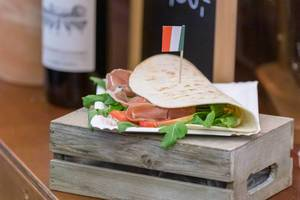 Italian food: Piadina Romangola with Parma ham, salad, cream cheese, pesto and fresh  tomatoes on a wooden box