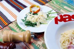 Italienische Küche: Parmesan-Käse in Scheiben mit Petersilie und Spaghetti Carbonara